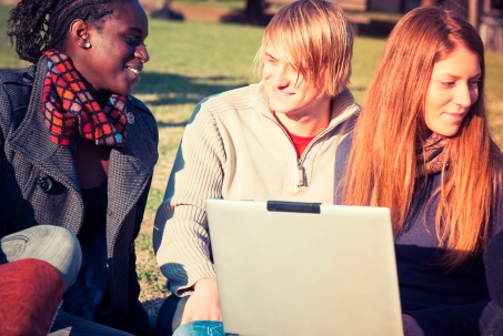 International students in a park with a laptop